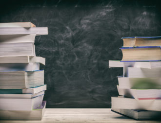 Back to school. Books stacked on black board background