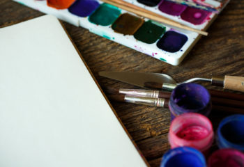 Art of Painting. Painting set: paper, brushes, paints, crayons, watercolor, acrylic paint on a wooden background