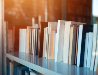 Books on library shelf through window, selective focus