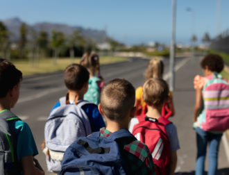 Rear view of a diverse group of schoolchildren walking along a road to elementary school together in the sun carrying their schoolbags