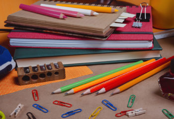 Horizontal composition with school supplies on table. Pencils and colored pencils, paperclips, sharpener, notebooks and red ink on recycled paper background. Back to school concept.
